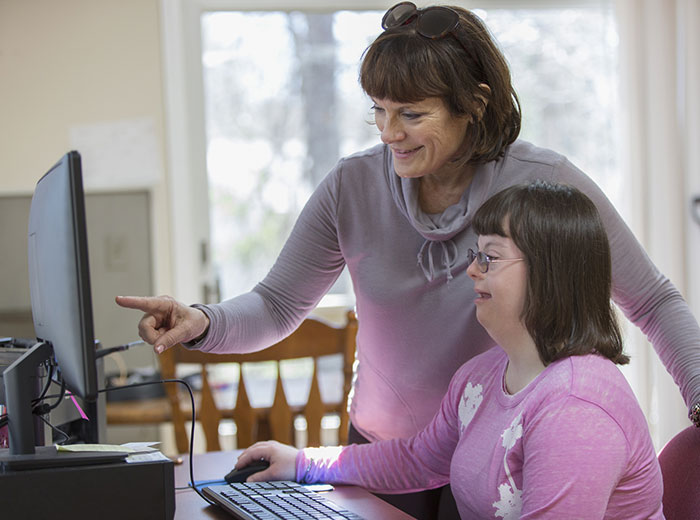 Woman helping young girl with computer