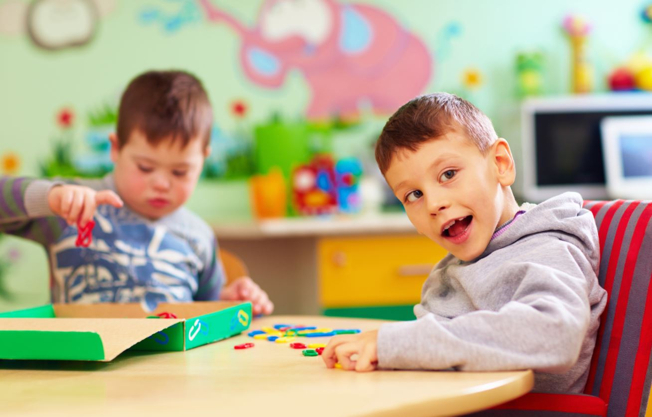 Two little boys sitting at a table in a colorful classroom, working together on a puzzle